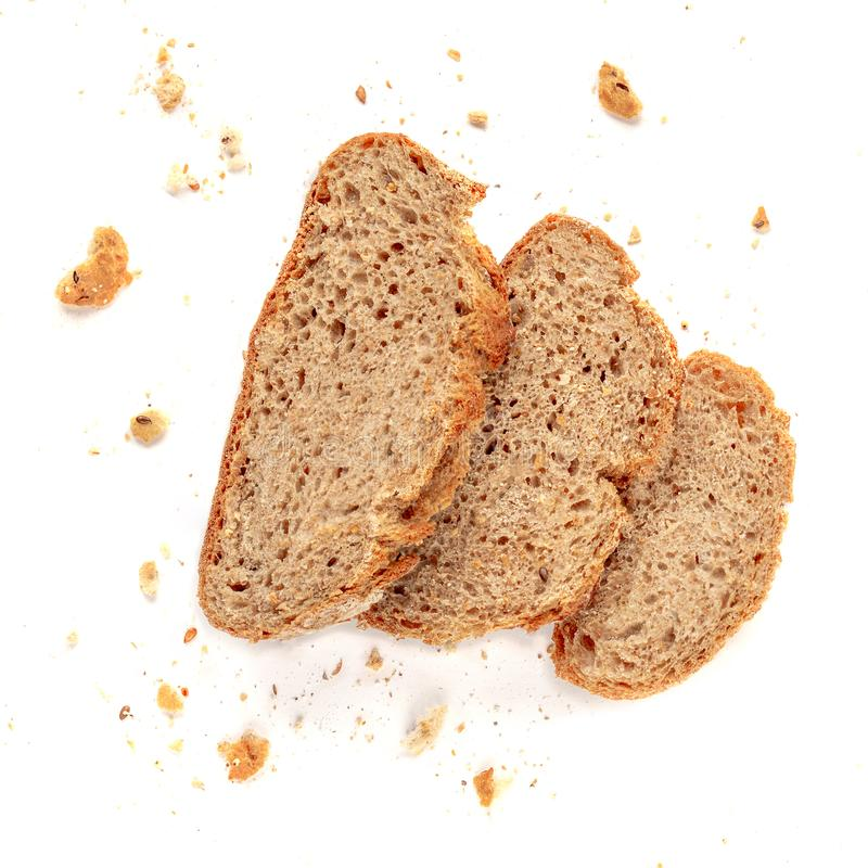 Three slices of toast bread with crumbs isolated on white background. Cutted wholegrain bread. Top view stock photos