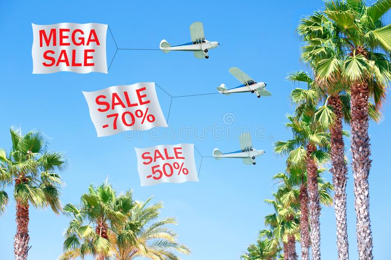 Three small aircraft towing banners with SALE stock images