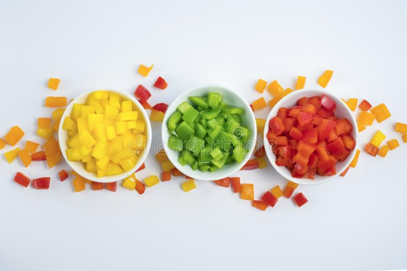 Three small bowls of chopped paprika with spread pieces of mixed paprika on the background stock photos