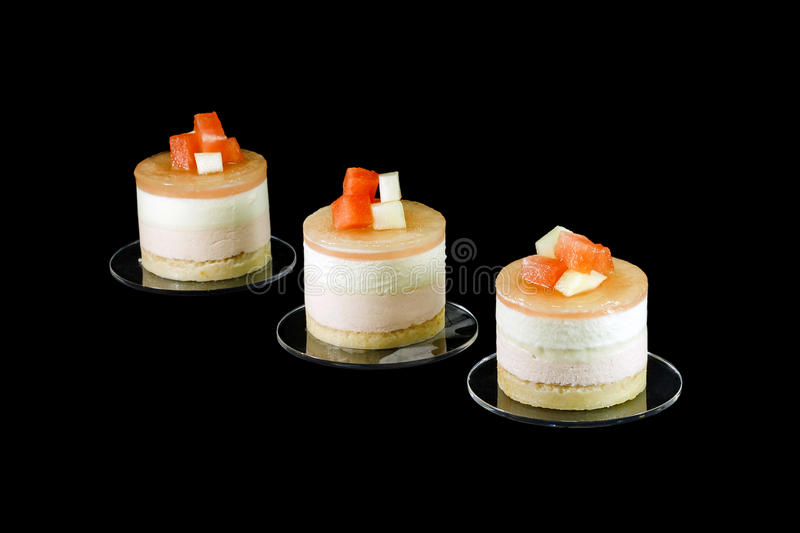 Three small cakes decorated with different fruits. Three small cake decorated with different fruits isolated on black stock image