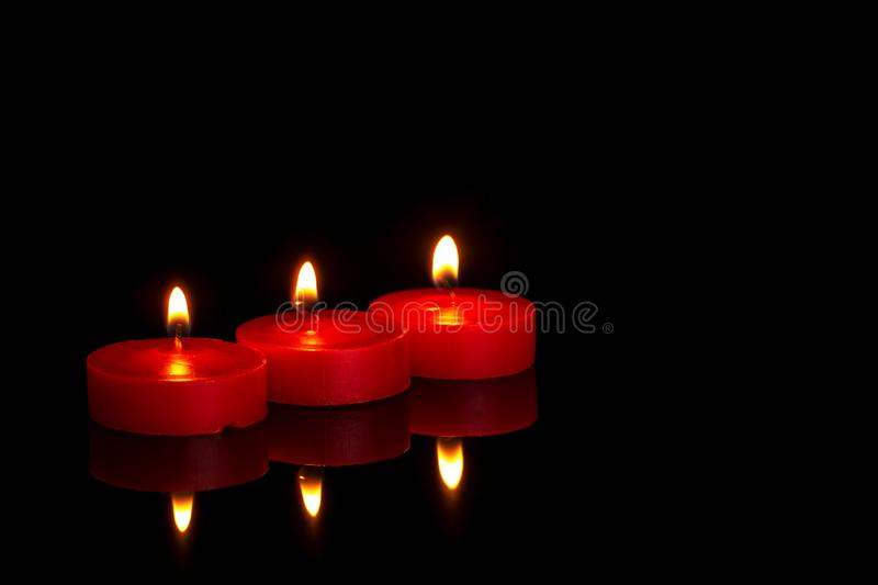 Three small red candles, tealights, burning at night on black. In memoriam or religious maybe. royalty free stock photo