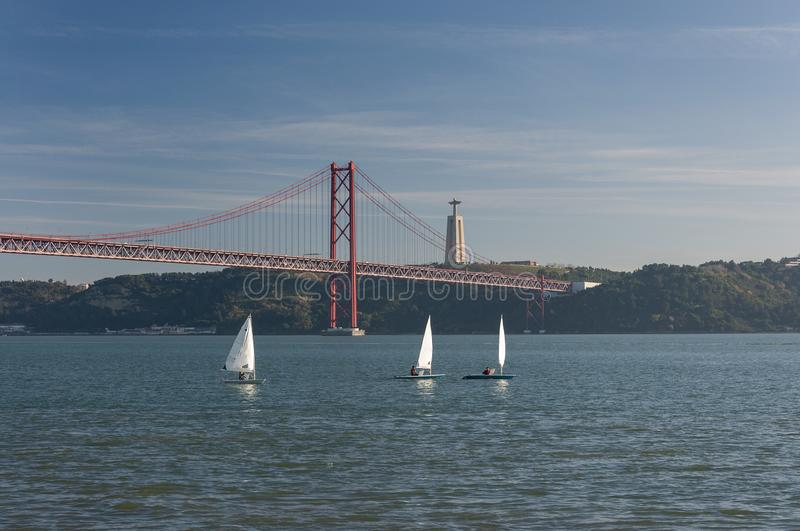 Three small sailing boats at the Tagus River with the 25 of April bridge on the background in the city of Lisbon royalty free stock image