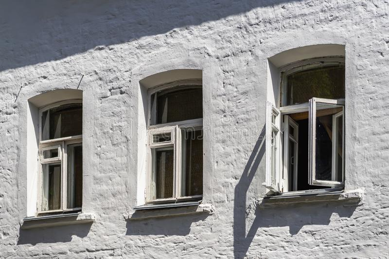 Three small windows on the facade of an old brick house painted with white paint. Three small wooden windows on the facade of an old brick house painted with stock image