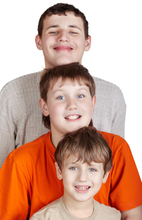 Three smiling boys stand one after another stock photo