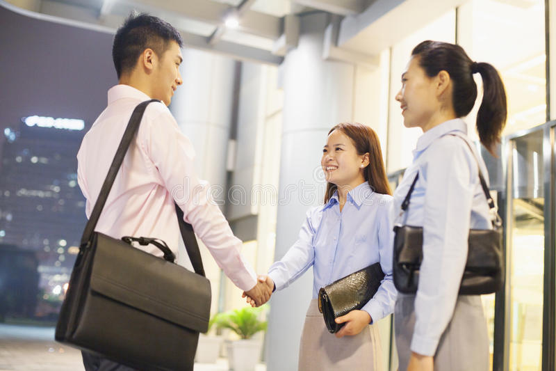 Three smiling business people handshaking outside the office at night stock images