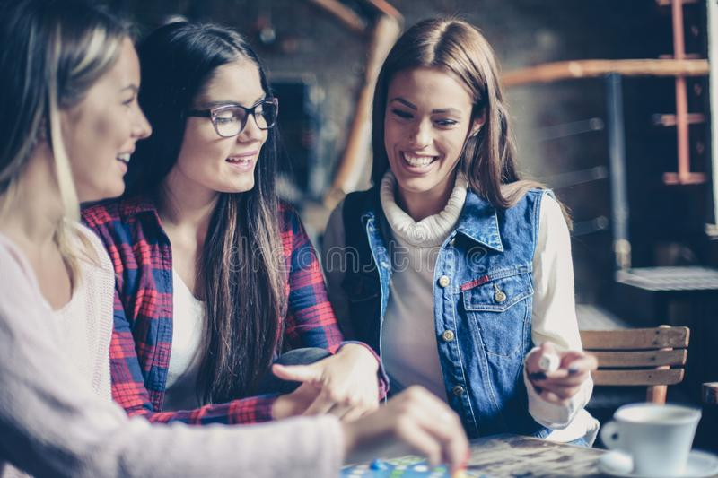 Three smiling cheerful girls playing board game. royalty free stock images