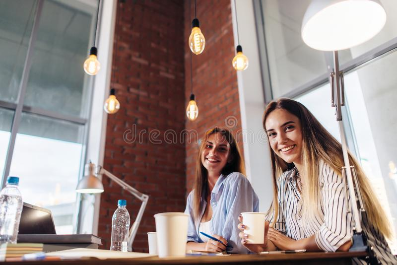 Three smiling female college students working on project together in classroom royalty free stock images