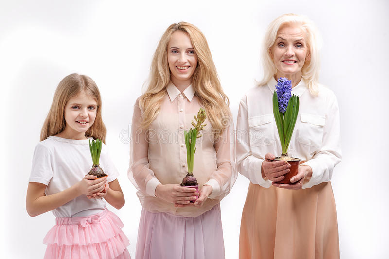 Three smiling female persons with plants. Different periods of life. Happy smiling ladies are holding flowers in flowerpots. Portrait. Isolated stock photos