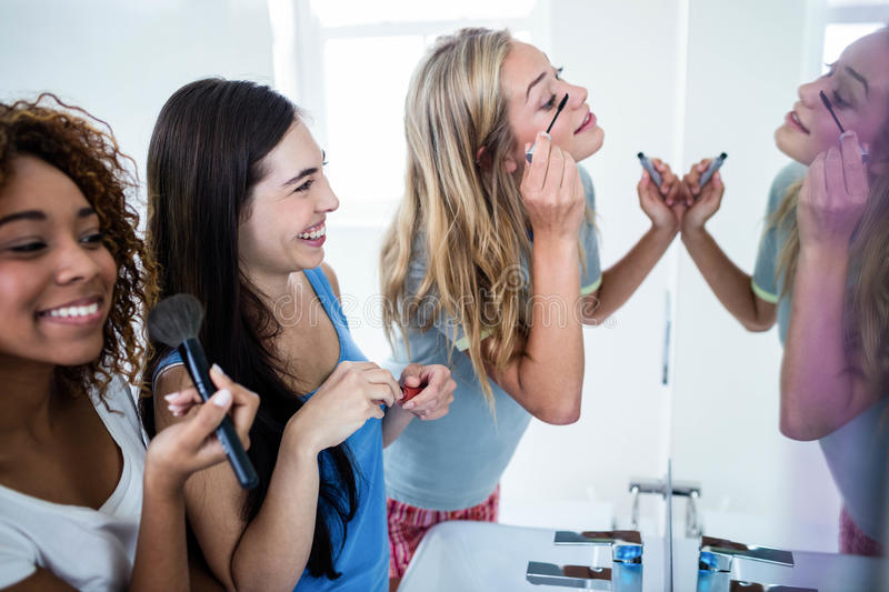 Three smiling friends putting makeup on together stock images