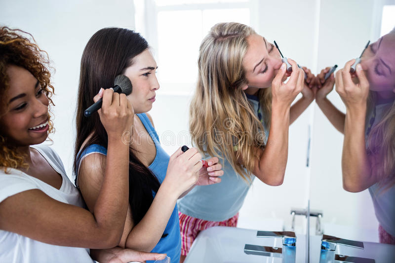 Three smiling friends putting makeup on together stock image