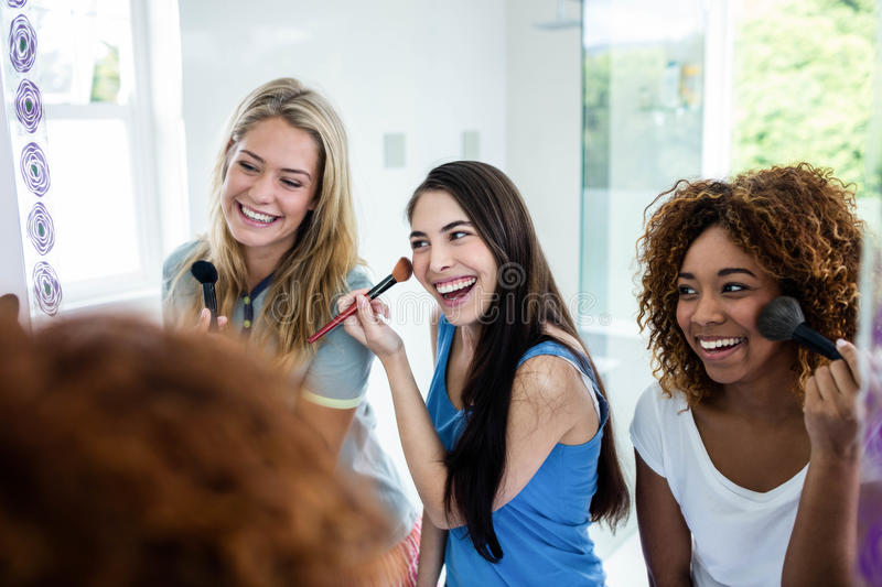 Three smiling friends putting makeup on together stock photos