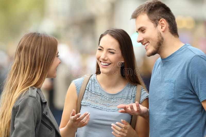 Three smiling friends talking standing on the street royalty free stock photography