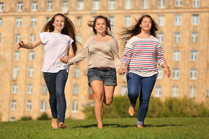 Download Three Smiling Girls Run At Grass And Hold Hands Stock Image - Image: 27753975