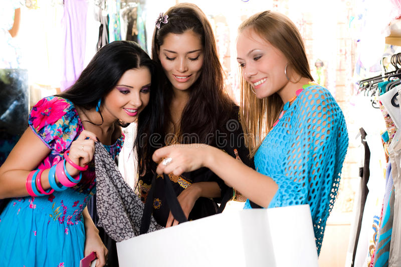 Three smiling girls are shopping royalty free stock image