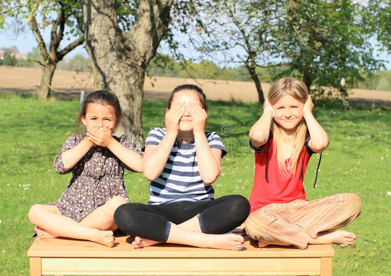 Three smiling girls sitting on the table royalty free stock photo