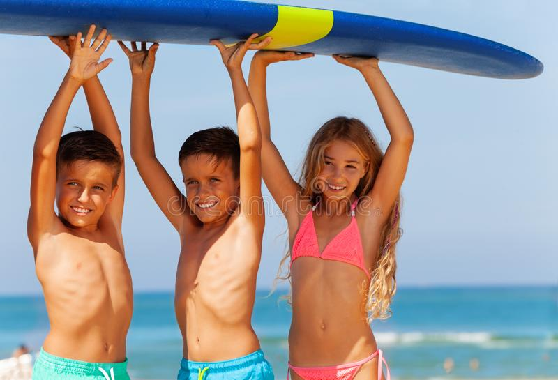 Three smiling kids boys and girl carry surfboard royalty free stock photos