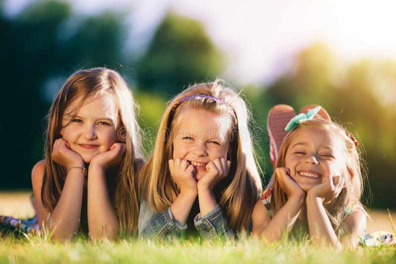 Three smiling little girls laying on the grass in the park. Childhood friendship. Sisterhood royalty free stock image