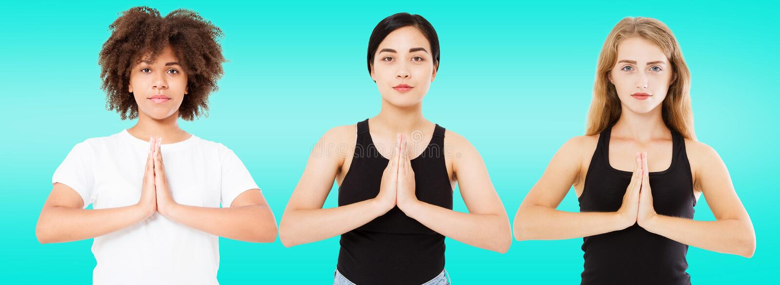 Three smiling multiracial women with different types of skin: caucasian, african american and asian girls in namaste pose isolated stock image