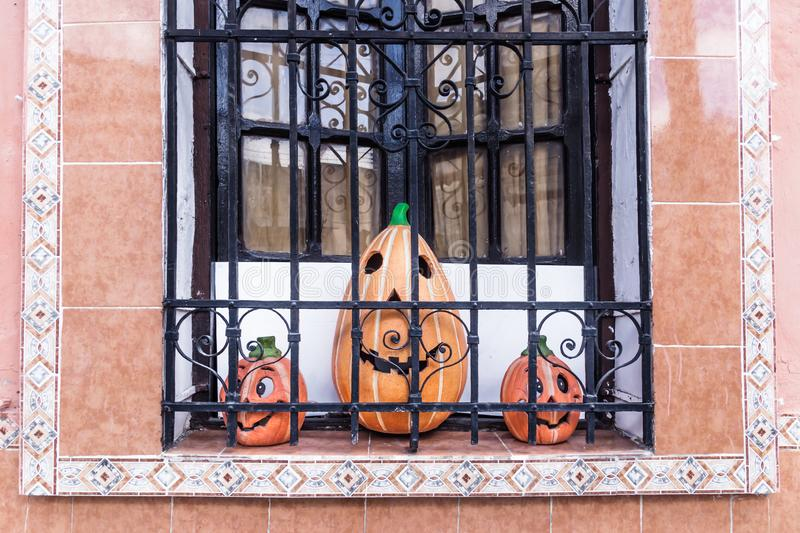 Three smiling pumpkins in a colonial window, Merida, Mexico. Three smiling pumpkins in a colonial window with traditional tiles, Merida, Mexico royalty free stock image