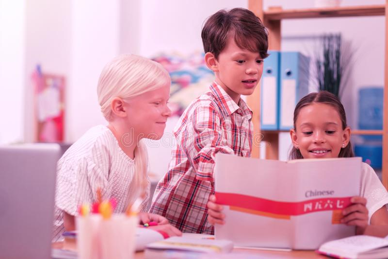 Three smiling pupils learning chinese in the classroom. Chinese class. Three smiling pupils learning chinese language with chinese workbook in the classroom royalty free stock photo