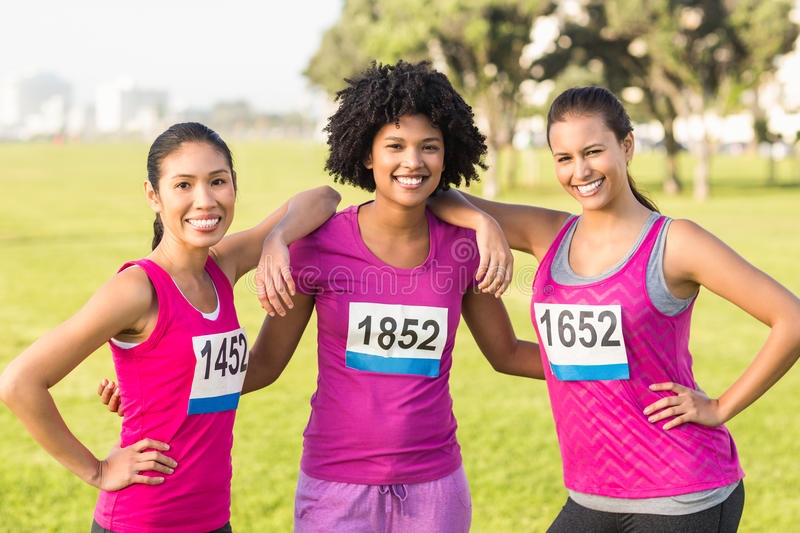 Three smiling runners supporting breast cancer marathon royalty free stock photos