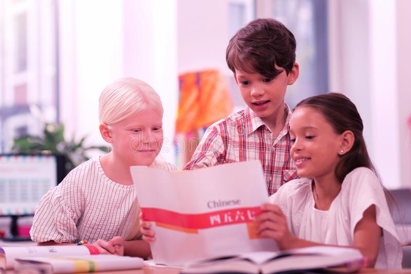 Three smiling schoolchildren looking at chinese workbook. Learning chinese. Three smiling schoolchildren looking for new words in their chinese workbook royalty free stock photography