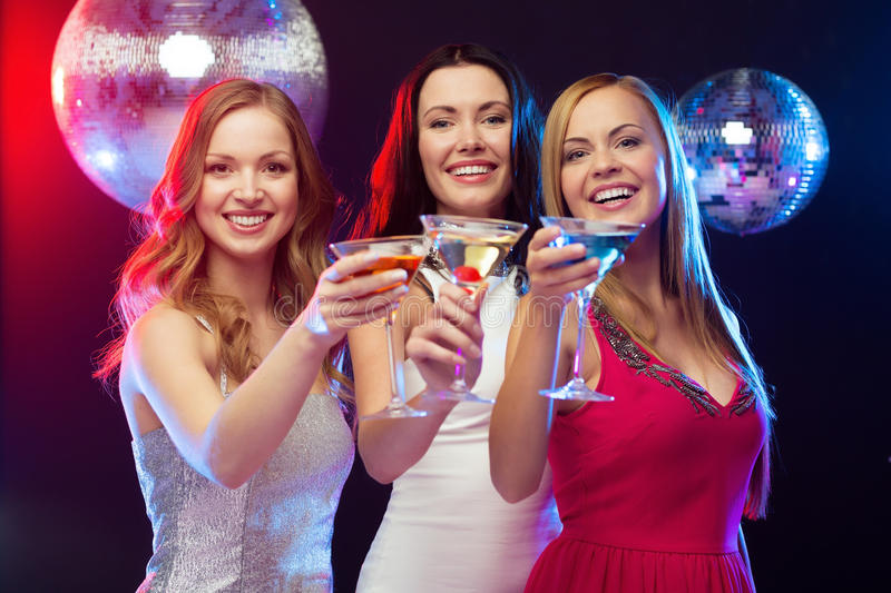 Three smiling women with cocktails and disco ball. New year, celebration, friends, bachelorette party, birthday concept - three women in evening dresses with royalty free stock photography