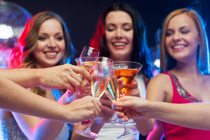 Three smiling women with cocktails and disco ball. Party, celebration, friends, bachelorette and birthday concept - three beautiful women in evening dresses with stock photos