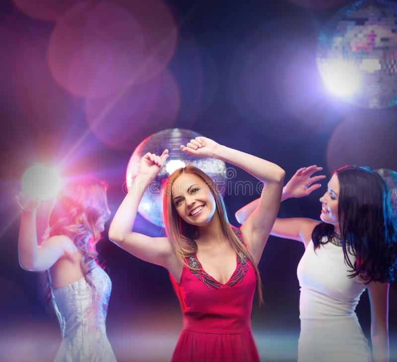 Three smiling women dancing in the club. Party, celebration, friends, bachelorette party, birthday concept - three beautiful women in evening dresses dancing in stock image