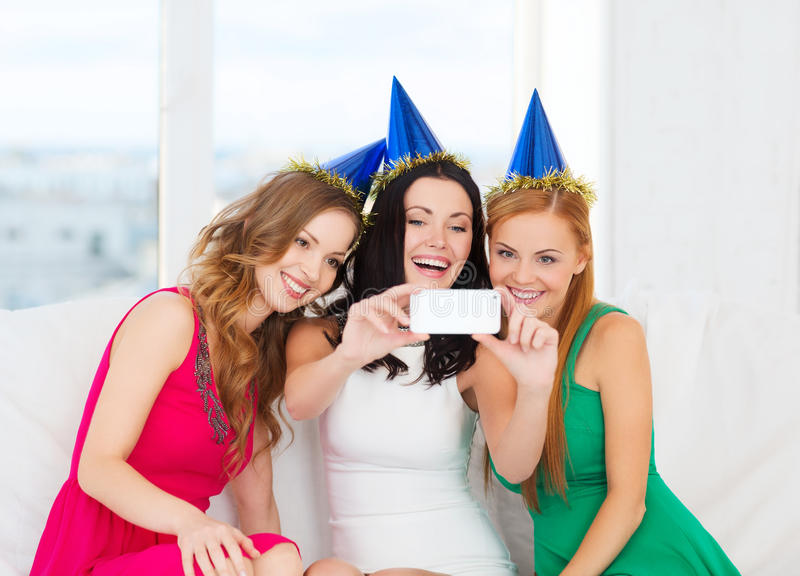 Three smiling women in hats having fun with camera stock photo