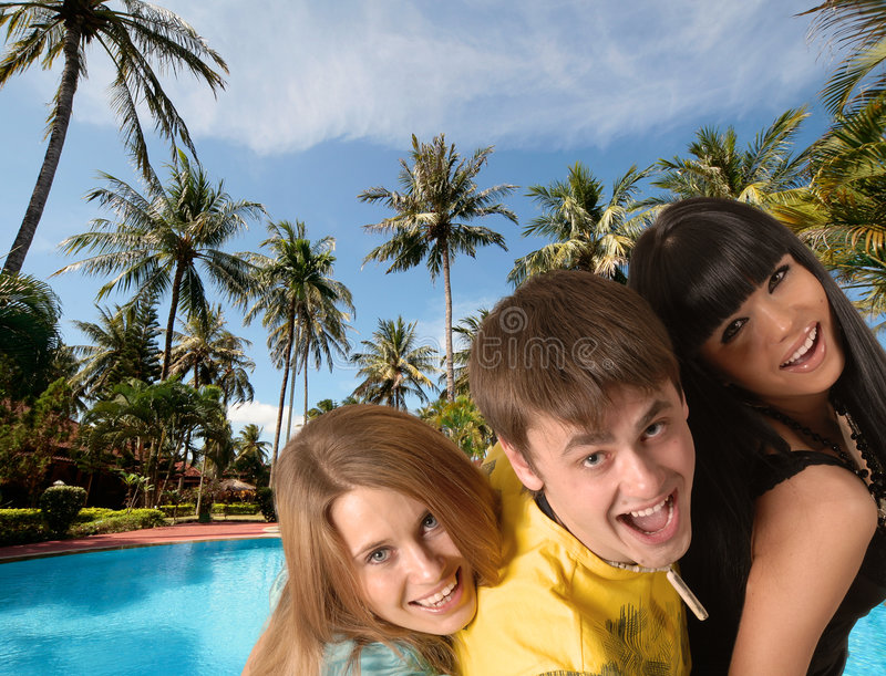 Three smiling young people stock images