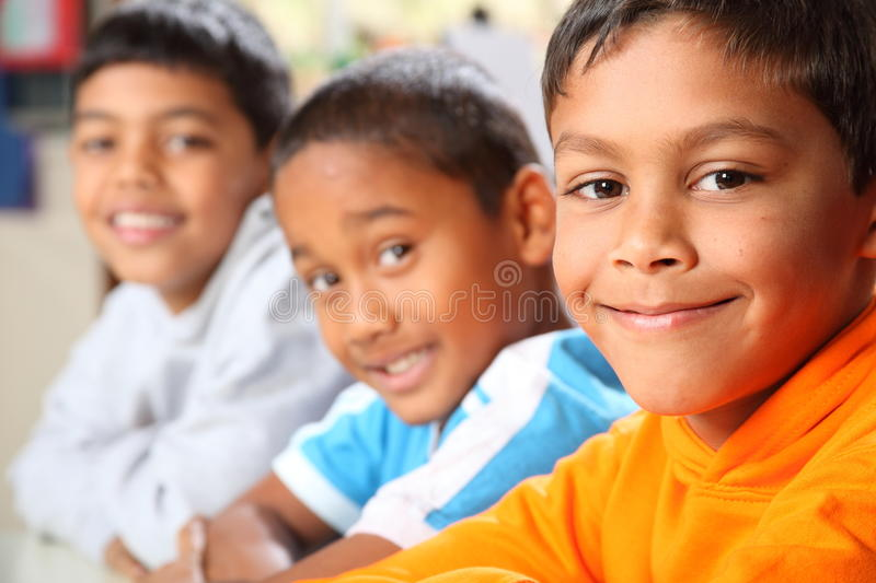 Three smiling young primary school boys sitting in