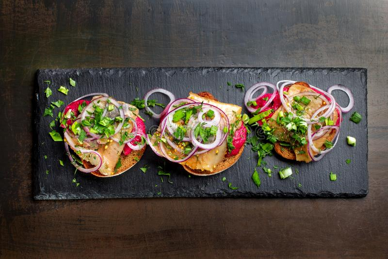 Three smoked salmon sandwich laid out on a black slate. stock images