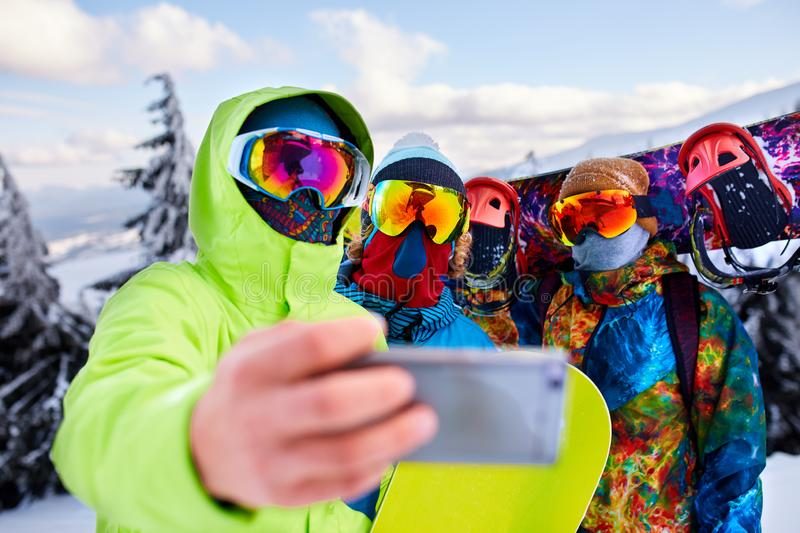 Three snowboarders taking selfie with smartphone camera at ski resort. Friends photographing for social network sharing royalty free stock photo
