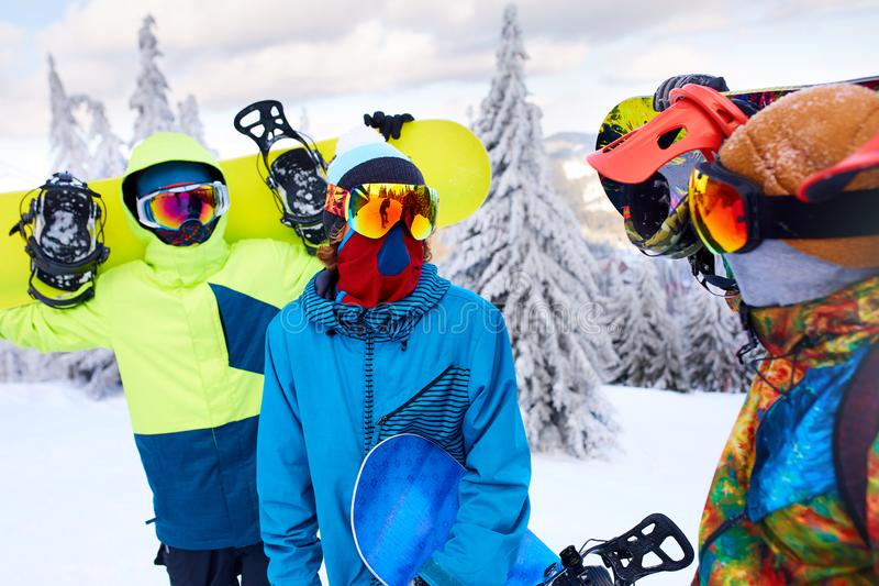 Three snowboarders walking at ski resort. Friends climbing to mountain top carrying their snowboards through forest for stock photos