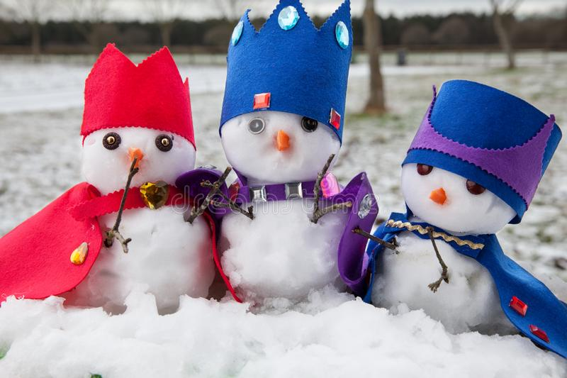 Three snowmen kings dressed with crowns and capes royalty free stock photos