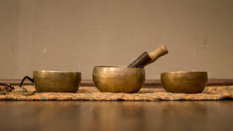Three sound bowls on wooden floor stock image