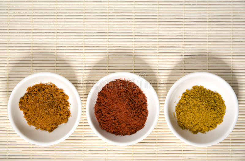 Three spices in bowls on straw mat stock photography