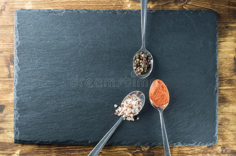 Three spices in spoons view on a background of slate and wood stock image