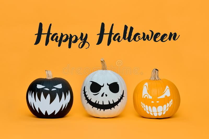 Three Spooky Halloween pumpkins with scary face expressions over orange background. Halloween backdrop. stock image