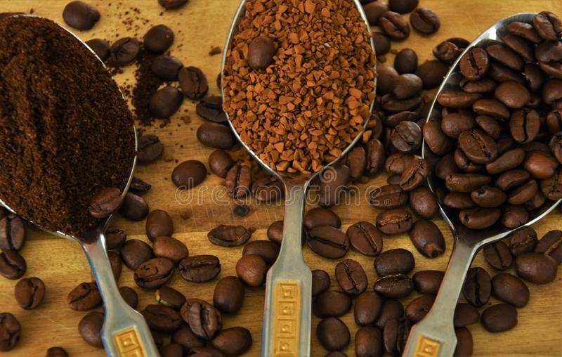 three spoons with coffee, grains, instant, and ground coffee stock image