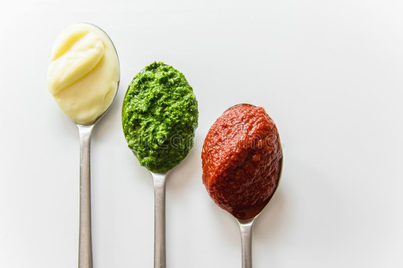 Three spoons with different condiments - mayonnaise, tomato sauce and pesto. On white background stock photos