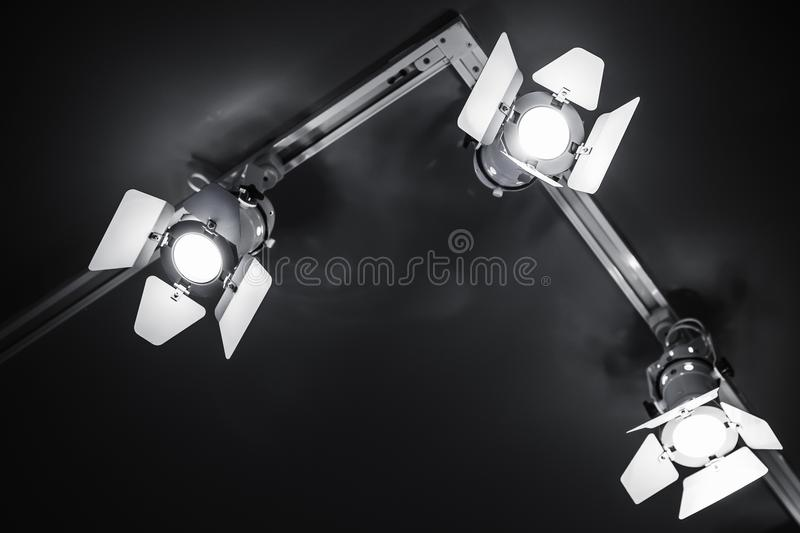 Three spot lights in metal body over black stock images