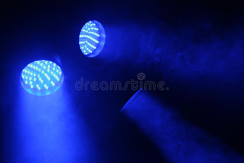 Three spotlights shine with blue light stock photo