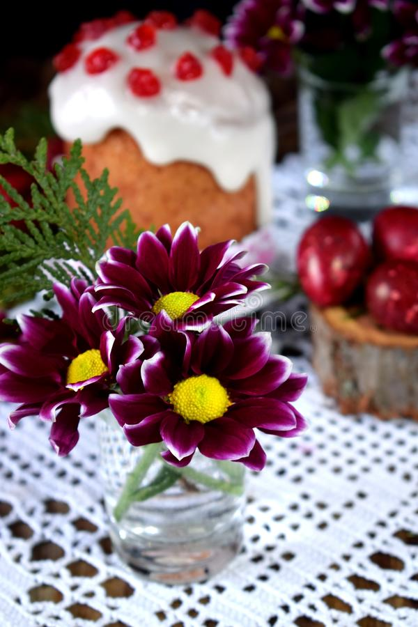 Three spring flowers. Easter cake and red coloured eggs in the background. stock images