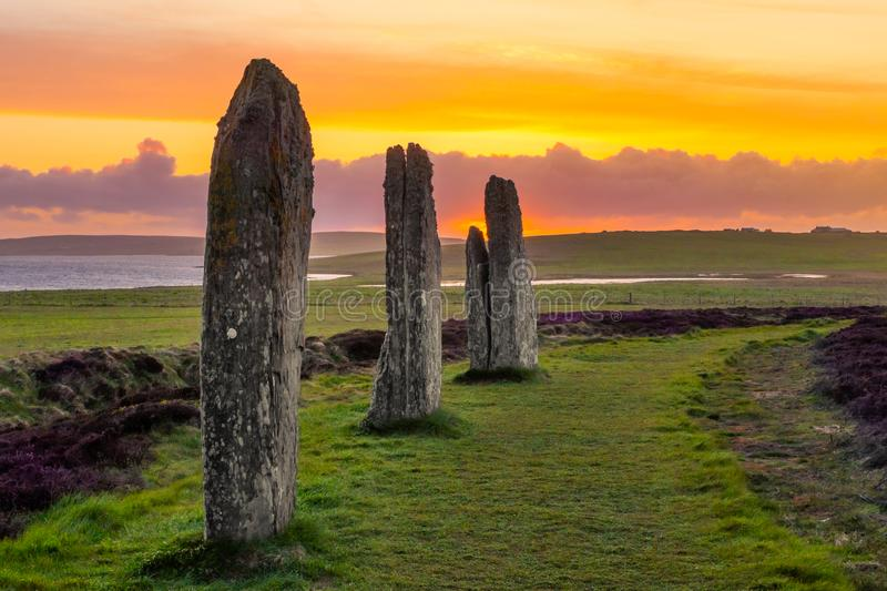Three standing stones of the Ring of Brodgar. Three standing stones of the ancient and mysterious Ring of Brodgar in the Orkney Islands, Scotland, as the sun stock image