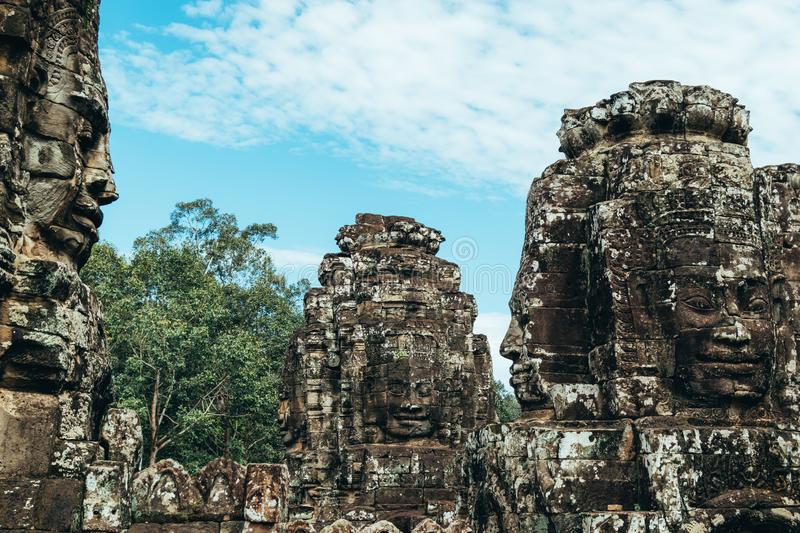 Three statues carved with face shapes on four sides on the roofs of the ruins of the Bayon temple in Ankgor Thom, Cambodia -. UNESCO World Heritage Site 1992 royalty free stock photography