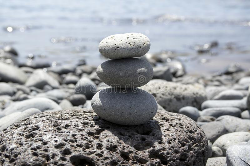 Three stone cairn tower on Madeira seacoast, poise stones, rock zen sculpture, light grey pebbles, blue ocean background. Volcanic pebbles stock photography
