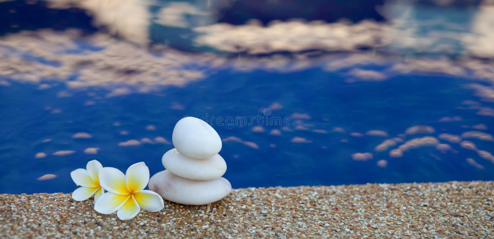 Three stones. With flowers placed near the water stock image