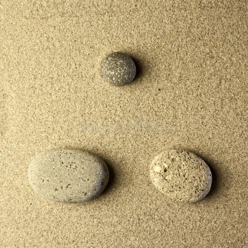 Three stones in the sand. Golden colors stock image